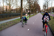 In Utrecht fietst een man op een groene ligfiets over het fietspad bij bedrijventerrein Rijnsweerd.<br /> <br /> In Utrecht a man cycles on a recumbent bike on a bike lane.