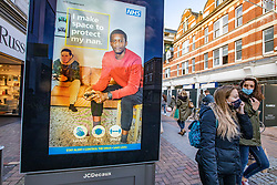 © Licensed to London News Pictures. 02/11/2020. London, UK. Shoppers walk past an NHS Covid-19 information display in Kingston Town centre in South West London. Kingston was busy with shoppers today, some doing early Christmas shopping with only two days left before another national lockdown after Prime Minister Boris Johnson announced on Saturday new Covid-19 restrictions for England from Thursday, with pubs, restaurants, non-essential shops and gyms to close. Later the Prime Minister will give a statement to the commons as he warns MPs that deaths from Covid-19's second wave could be twice as high as the first ahead of MPs voting on the Government's 4 week lockdown measures. Photo credit: Alex Lentati/LNP