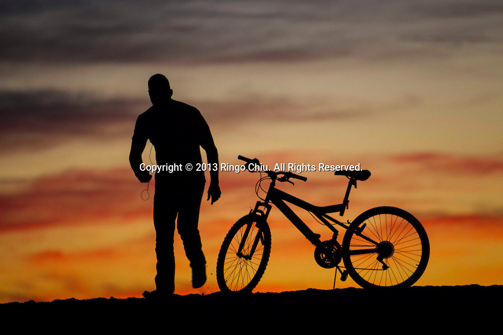 A man with his bike is seen during the sunset on Sunday December 1, 2013 at Venice Beach, California.(Photo by Ringo Chiu/PHOTOFORMULA.com)(Photo by Ringo Chiu/PHOTOFORMULA.com)