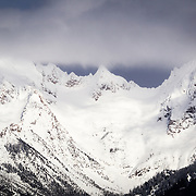 The Sisters Peaks in the Cascades break free of a winter storm and open to sunlight.