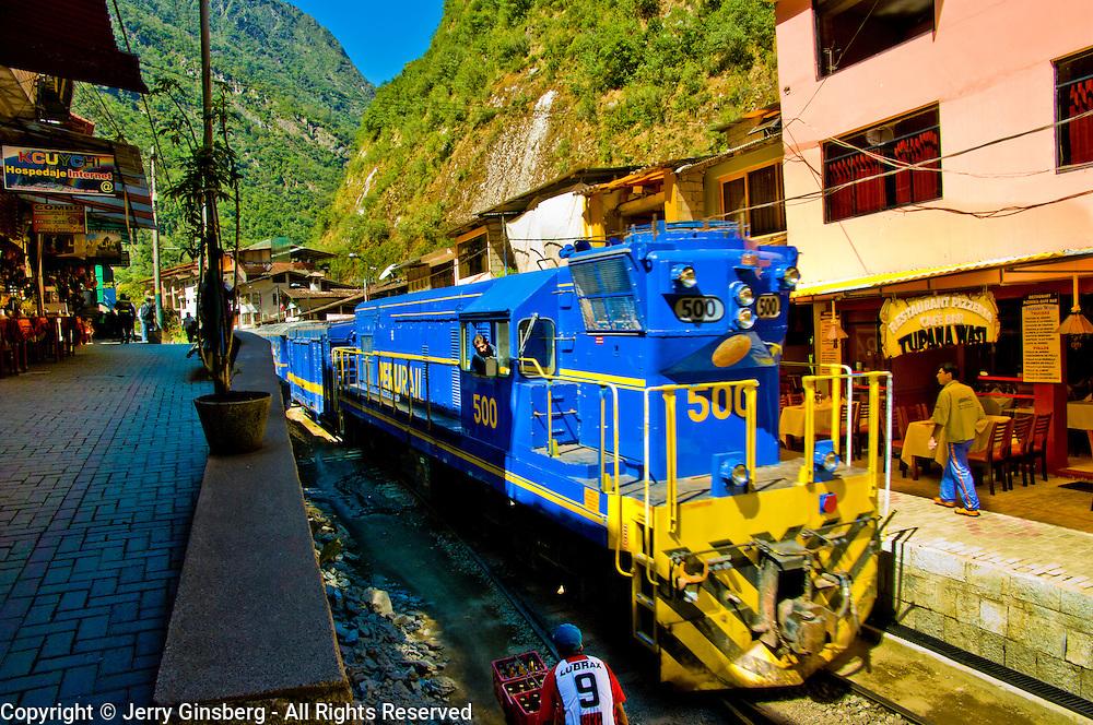 Passenger trains run right down the main street of the small village of Aguas Calientes, gateway to famed Machu Picchu, Peru.