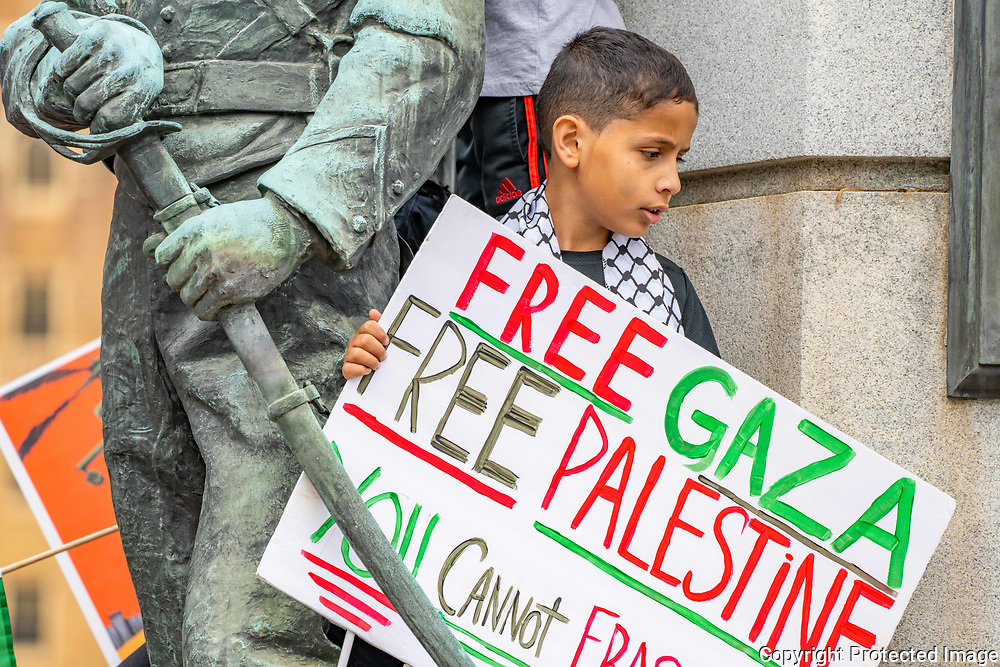 Yusif Abdelaziz, 10, of Allentown, Pennsylvania, watches the Palestine solidarity rally from the top of the war memorial in downtown Allentown, Pennsylvania.