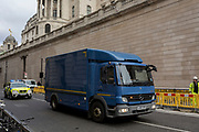 An HGV lorry carrying something inside of high-value (often bullion or cash), is driven at speed under police escort, in a convoy on Princes Street and passing beneath the tall walls of the Bank of England, on 4th February 2020, in the City of London, England.