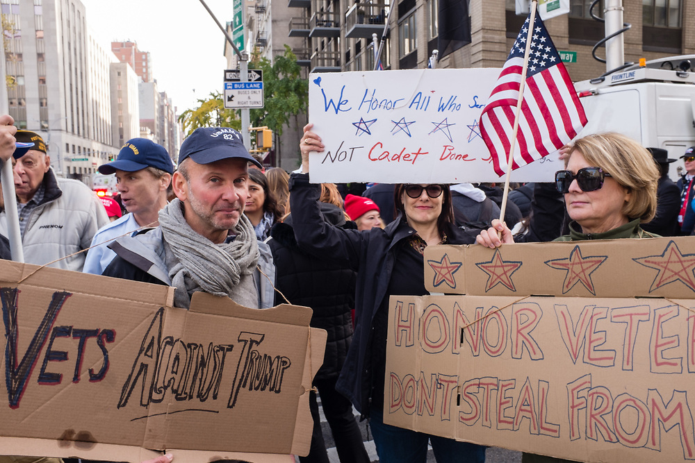 """New York, NY - 11 November 2019. New York City's Veterans Day Parade, today marking the 100th anniversary of the armistice ending the fighting of the first World War, was attended by a number of people protesting President Trump, who spoke at the opening ceremony, and a smaller number of pro-Trump supporters. A man carries a sign reading """"Vets Against Trump,"""" while women hold signs reading """"We honor all who served not Cadet Bone Spurs"""" and """"Honor Veterans Don't steal From [them]"""""""