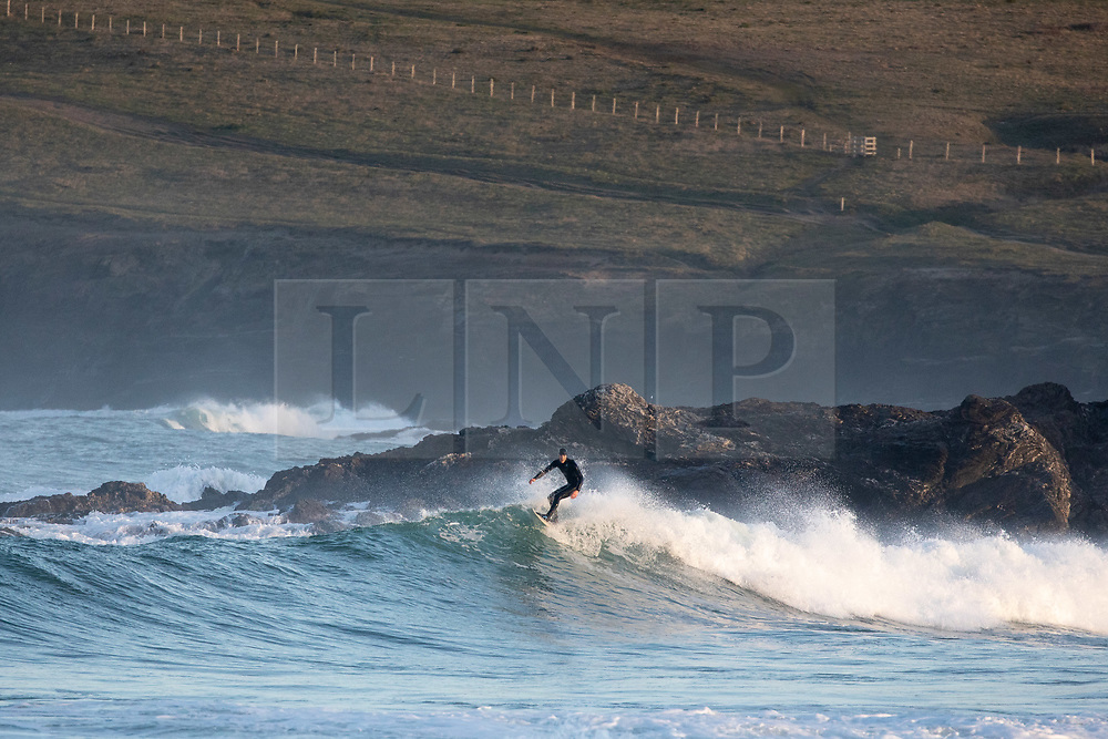 © Licensed to London News Pictures. 07/04/2020. Padstow, UK. Surfers catch waves at Constantine Bay on the north coast of Cornwall shortly after the sunrise this morning. The weather in the south-west is forecast to be another warm, clear day. Photo credit : Tom Nicholson/LNP