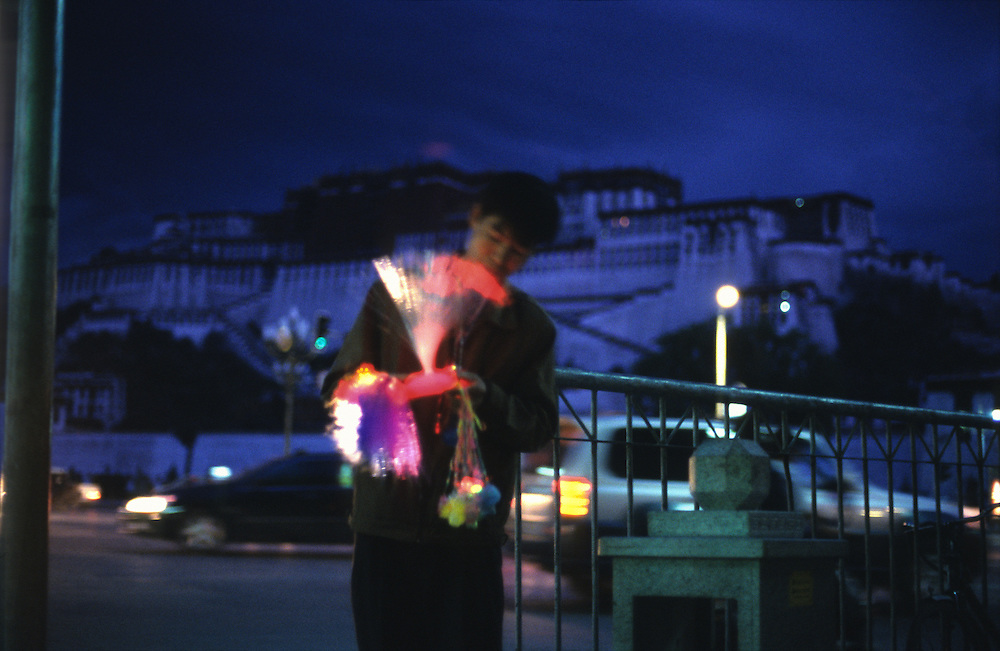 A street vendor sells glow sticks  across the road from the Dalai Lama's former residence; the Potala Palace in  Tibet's capital city, Lhasa.