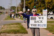"""19 SEPTEMBER 2020 - ALTOONA, IOWA: MARGE KESSLER waves at passing motorists during a pro-police rally near the police station in Altoona, a suburb of Des Moines. About 30 people attended an """"Uplifting Our Police"""" rally to show support for not just Altoona police, but law enforcement across the country.    PHOTO BY JACK KURTZ"""