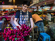 18 FEBRUARY 2016 - BANGKOK, THAILAND: A rose vendor does business in front of the Trimurti Shrine on Thursday night. Every Thursday night, starting just after sunset and peaking at 21.30, hundreds of Bangkok single people, or couples seeking guidance and validation, come to the Trimurti Shrine at the northeast corner of Central World, a large Bangkok shopping mall, to pray to Lord Trimurti, who represents the trinity of Hindu gods - Brahma, Vishnu and Shiva. Worshippers normally bring an offering of red flowers, fruits, one red candle and nine incense sticks. It's believed that Lord Trimurti descends from the heavens at 21.30 on Thursday to listen to people's prayers. Although most Thais are Buddhists, several Hindu traditions have been incorporated into modern Thai Buddhism, including reverance for Trimurti.       PHOTO BY JACK KURTZ