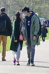 © Licensed to London News Pictures. 16/03/2020. London, UK. A couple wearing face masks are seen kissing in St James's Park. Due to Coronavirus spread in London, less people are visiting parks to avoid crowded area. Photo credit: Dinendra Haria/LNP
