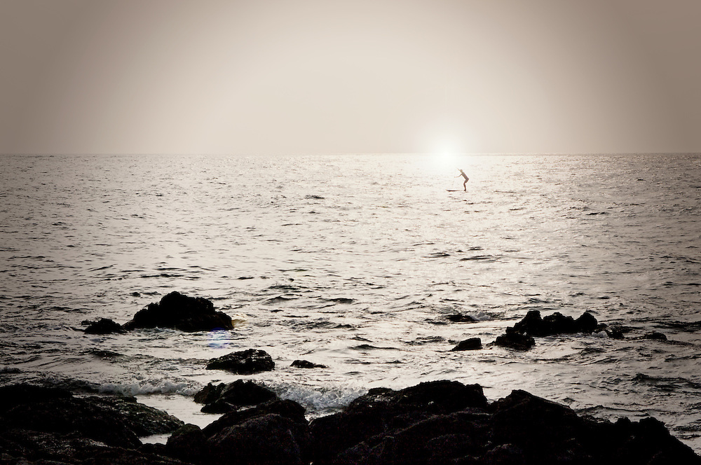 A lone paddle boarder paddles on the ocean during sunset. Lava rock can be seen in the foreground.