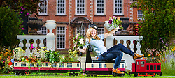 © Licensed to London News Pictures. 12/09/2019. Harrogate UK. Garden designer Sarah Richardson a florist from Leafy Couture sits on the Newby Hall model train in the recreated Newby Hall garden display at the Harrogate garden show which opens tomorrow in Yorkshire. Photo credit: Andrew McCaren/LNP