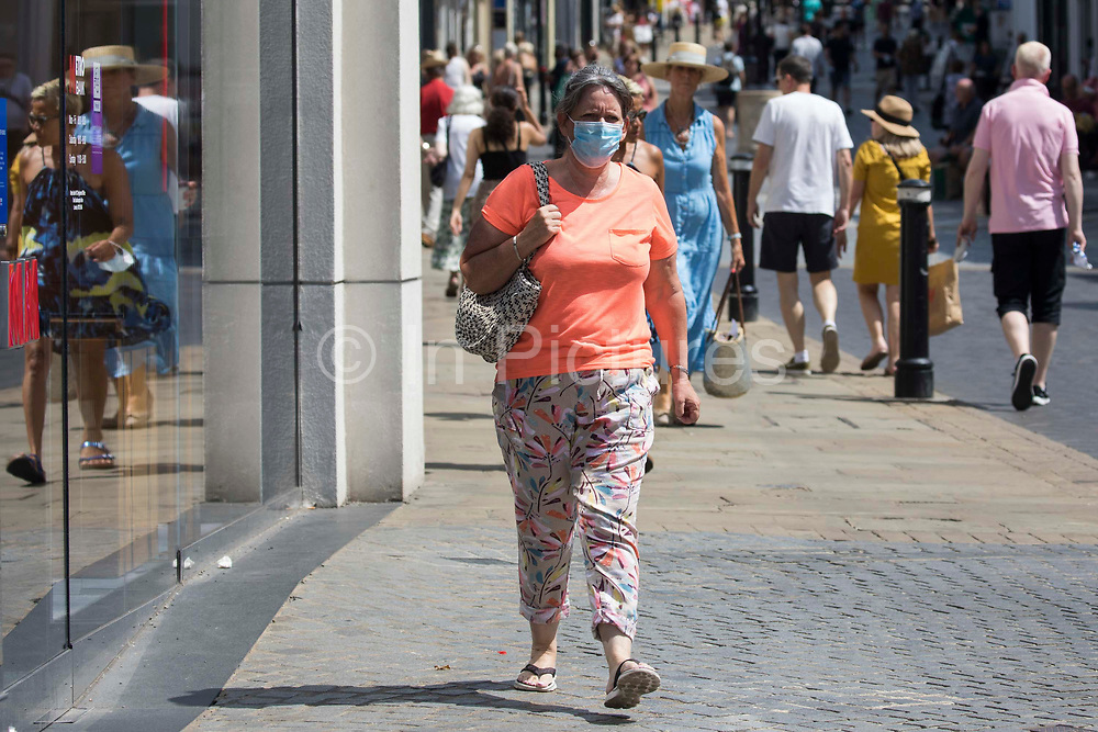 Shoppers, some of whom wearing face coverings, are pictured on Freedom Day, when the UK government lifted almost all remaining Covid-19 restrictions in England, on 19th July 2021 in Windsor, United Kingdom. Social distancing restrictions have been removed and face coverings are no longer required by law, although their use is recommended in crowded and enclosed spaces. Cases of the coronavirus are now expected to surge across the UK, which currently has the highest rate of daily recorded Covid-19 cases in the world.
