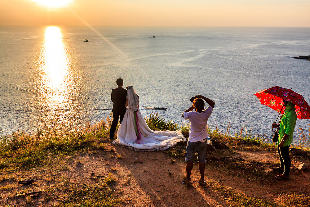 Wedding couple in Phromthep Cape in Phuket, Thailand. Looking at sunset is regarded to bring happiness and love.
