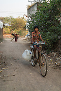 A boy cycles to the iJal water station with his water can in Gorikathapalli, a remote village in Warangal, Telangana, India, on 22nd March 2015. Safe Water Network works with local communities that live beyond the water pipeline to establish sustainable and reliable water treatment stations within their villages to provide potable and safe water to the communities at a nominal cost. Photo by Suzanne Lee/Panos Pictures for Safe Water Network