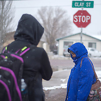 Snow falls on Sally J. Garcia, right, and her friend while waiting for the Gallup Express at the corner of Clay Street and Jay Street in Gallup Monday.