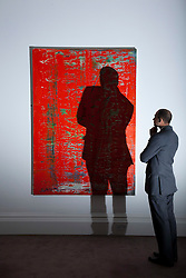 © Licensed to London News Pictures. 01/02/2012. LONDON, UK. A member of Sotherby's staff looks at Gerhard Richter's, Abstraktes Bild, 'rot', ahead of an auction of Impressionist and Modern Art held on the 15th of February 2012. The piece is estimated to raise £2,500,000-3,500,000. Photo credit: Matt Cetti-Roberts/LNP