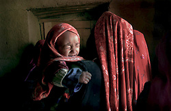 An Afghan woman and her child wait to be seen by a doctor  from the non-governmental aid agency Medicine San Frontiers near the village of Anbar Somuch in the Bamiyan district of Afghanistan July 31, 2002.  USA. Infant mortality in Afghanistan in 2000 was 165 per 1,000. live births - one of the highest figures in the world, according to the United Nations International Children's Fund (UNICEF). More than one if four children die before age 5. The U.S. infant mortality rate is 7 per 1,000. Half Afghanistan's children suffer from malnutrition. (Photo  by Ami Vitale)