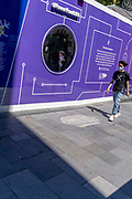 A man wearing a cross on his t-shirt walks past a mirror, part of a hoarding that screens off refurburshment works in the West Ends Leicester Square, on 16th July 2021, in London, England.
