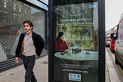 © Licensed to London News Pictures. 29/03/2021. London, UK. A man walks past the government's 'Thinking of going in? Keep working from home if you can.' latest advertising campaign poster in north London as lockdown restrictions across the UK are easing this week. The adverts remind the public that they must stay outside when meeting others. Photo credit: Dinendra Haria/LNP