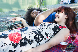 Couple lying on blanket at lakeshore in the English Garden, Munich, Germany