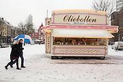 Een man en vrouw lopen langs de oliebollenkraam op de Neude in Utrecht.<br /> <br /> A man and woman are walking in the snow at the Neude Utrecht.