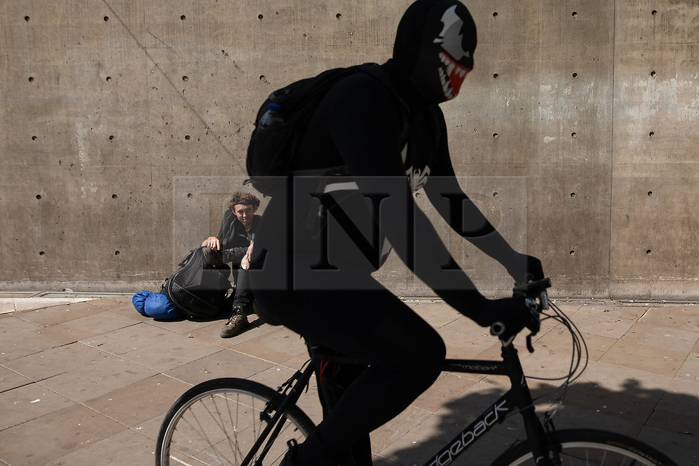 © Licensed to London News Pictures . 20/05/2020 . Manchester , UK . A man rests against a concrete wall in sunshine in Piccadilly Gardens in Manchester City Centre as another wearing a morph suit cycles past . On the hottest day of the year so far independently run coffee shops and bars are open and trading with social distancing measures applied , after a period of being shut in an effort to reduce the spread of Covid-19 . Photo credit : Joel Goodman/LNP