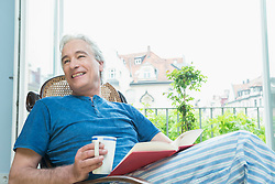 Mature man sitting with book in rocking chair, smiling