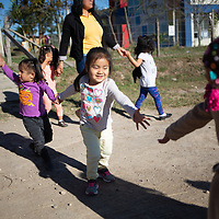 """Children arrive for school at the COMSA International School in Marcala, Honduras. <br /> <br /> <br /> Education is a core concern for the leadership and membership of the COMSA coop and the COMSA International School is a long-term initiative by the coop to improve the education of coffee farmers' children in the area. Children are accepted from the age of six months in a pre-kinder, and go up to 18 years old, before going to university. The school has had a lot of success and attention.<br /> The school questions traditional approaches to education and uses some unconventional techniques such as the Glenn Doman method. The children all learn English, French, German and Japanese.<br /> Douglas Penalba, the Glenn Doman method coordinator for the school, explained that """"the Doman method was developed to help children - including children with special needs - to develop and progress in every area, for the children to reach their fullest potential"""". Children in the school play and develop in an atmosphere of freedom, with a high teacher to student ratio, they do well academically and they are unusually successful in languages. Most children at the school study with a grant, subsidised heavily by money from Fairtrade premiums."""