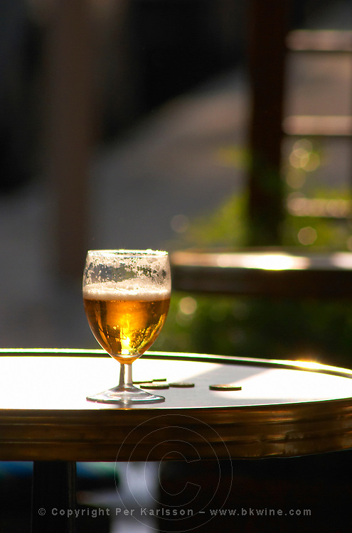 On a cafe table in the late afternoon sunshine a glass of beer with foam froth with sun backlighting the drink and some change coins on the table  Vienne, Isère Isere, France, Europe