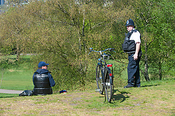 ©Licensed to London News Pictures 14/04/2020  <br /> Greenwich, UK. A police officer asking a man to move on. Sunny weather in Greenwich park, Greenwich, London as people get out of the house from coronavirus lockdown to exercise. Photo credit:Grant Falvey/LNP