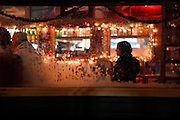 Holiday lights illuminate raindrops on the exterior of a barroom window on Dec. 31, 2020, New Year's Eve, at Sourdough Bar in Ketchikan, Alaska. Normally New Year's Eve is the establishments busiest day of the year, but COVID-19 has deterred business this year.