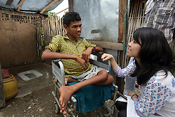 Sarah Nam (AYAD) Communications and Social Networking Officer, Department of Water Supply and Sewerage talk with Dik Bahadur Sarki who is in a wheelchair.  NEWAH built a special toilet for the needs of this disabled man.  At a NEWAH WASH water project in Puware Shikhar, Udayapur District, Nepal