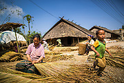 10 MARCH 2013 - ALONG HIGHWAY 13, LAOS:  A woman in a Hmong village on Highway 13 makes thatch for roofing while her son plays nearby. The paving of Highway 13 from Vientiane to near the Chinese border has changed the way of life in rural Laos. Villagers near Luang Prabang used to have to take unreliable boats that took three hours round trip to get from the homes to the tourist center of Luang Prabang, now they take a 40 minute round trip bus ride. North of Luang Prabang, paving the highway has been an opportunity for China to use Laos as a transshipping point. Chinese merchandise now goes through Laos to Thailand where it's put on Thai trains and taken to the deep water port east of Bangkok. The Chinese have also expanded their economic empire into Laos. Chinese hotels and businesses are common in northern Laos and in some cities, like Oudomxay, are now up to 40% percent. As the roads are paved, more people move away from their traditional homes in the mountains of Laos and crowd the side of the road living off tourists' and truck drivers.    PHOTO BY JACK KURTZ