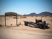 Rusted old car and sign for Solitaire rest stop and gas station, Namibia, Africa