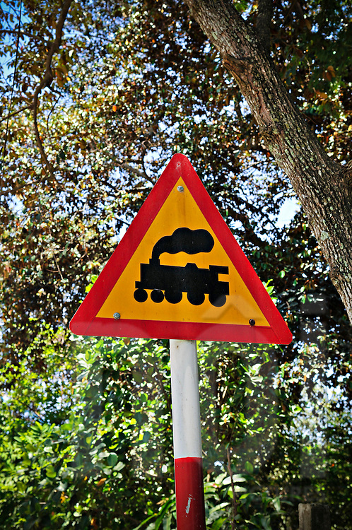 A triangular sign with a picture of a steam train indicates a railroad crossing ahead, Khanh Hoa province, Vietnam, Southeast Asia