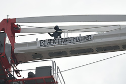©Licensed to London News Pictures; 18/03/2021, London UK; Police officers cordon off a car park next to a building site in Canning Town, East London, after a BLM protestor scaled a tower crane in support of the Black Lives Matter campaign at around 7.30 this morning : Photo credit, Steve Poston/LNP