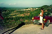 Stylish young woman looking at landscape view standing next to red British sports car on motoring holiday in Spain 1966