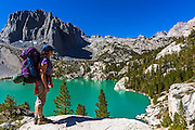 Backpacker at Second Lake under Temple Crag and the Palisades, John Muir Wilderness, California USA