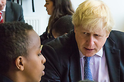 Michaela Community School, Wembley, London, June 23rd 2015. Mayor of London Boris Johnson visits the Michaela Community School, a Free School in Wembley that started taking students in September2014 after battling a certain amount of resistance from locals and unions. During the visit Head Teacher Katharine Birbalsingh took the Mayor on a tour of the school before he participated in a history lesson, prior to sitting down with pupils for brunch. PICTURED: Mayor of London Boris Johnson listens to one of the students at Michaela Community School.