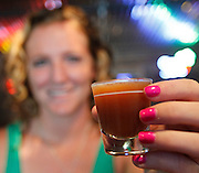 """Bartender Zoey Hill from New Athens holds up a specialty drink she created called """"Muddy Water"""".  It contains vodka and schnaps, plus other secret ingredients known only to Hill."""