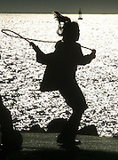 A girl skips rope in silhouette as the sun glistens off Puget Sound. (Jim Bates / The Seattle Times)