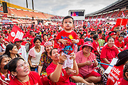 30 NOVEMBER 2013 - BANGKOK, THAILAND:   A family of pro-government Red Shirts hold up their baby so the infant can see the stage at a Red Shirt rally in Bangkok Saturday. Political faultlines in Bangkok, the Thai capital, hardened Saturday. Antigovernment factions repeated promises to strike at the heart of Bangkok Sunday and bring down the government while thousands of Red Shirts, who support the government, have come to Bangkok from their base in rural Thailand to defend the government. Prime Minister Yingluck Shinawatra has appealed for calm, but her opponents have rejected all requests for negotiations saying the only acceptable outcome is the eradication of the government.      PHOTO BY JACK KURTZ