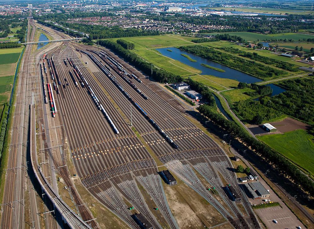 Nederland, Zuid-Holland, Zwijndrecht, 12-06-2009; Kijfhoek, rangeerterrein voor goederentreinen, overzicht van de verdeelsporen met onder in beeld de railremmen, spoorbrug van Dordrecht aan de horizon. De Betuweroute, die begint als Havenspoorlijn op de Maasvlakte, verbindt via Kijfhoek de Rotterdamse haven met het achterland. Kijkhoek huisvest Keyrail, exploitant Betuweroute en is in beheer bij ProRail.Het rangeeremplacement dient voor het sorteren van goederenwagons waarbij gebruik gemaakt wordt van de zwaartekracht, het heuvelen: de wagons worden de heuvel opgeduwd, bij het de heuvel afrollen komen ze, door middel van wissels, op verschillende verdeelsporen, railremmen zorgen voor het automatisch remmen van de wagons. Na het heuvelproces staan de nieuw samengestelde treinen op aparte opstelsporen..Kijfhoek, railway yard used by ProRail and Keyrail (Betuweroute operator). Kijfhoek connects via the Betuweroute (beginning as Havenspoorlijn on the Maasvlakte), through the port of Rotterdam with the hinterland. The shunting yard for sorting wagons makes use of gravity. The new trains are assembled on separate tracks.luchtfoto (toeslag), aerial photo (additional fee required).foto/photo Siebe Swart