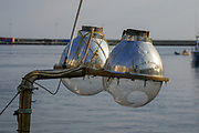 A lantern  on a bow of a small fishing boat. The light attracts the fish. Photographed in Greece
