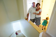 PRICE CHAMBERS / NEWS&GUIDE<br /> After a year of working on it, Habitat for Humanity home recipients Jim and Lisa Wolfgang smile as their daughters Isabella and Sophie, 3, explore their completed Teton Village home on July 19, 2013.