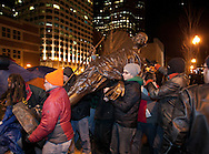 Boston, MA 12/08/2011.A statue of Gandhi brought in from the Peace Abbey in Sherborn is carried out of Dewey Square during the Occupy Boston protest on Thursday night..Alex Jones / www.alexjonesphoto.com