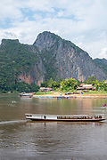 Local boat drivers ferry tourists across the Mekong River to the famous Pak Ou Caves, Laos.