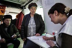 Doctor Victoria Pogorelova writes a prescription for medicines for Alexander and Nadezhda Buryak during a mobile clinic consultation held in a van in a neighbourhood of Debaltsevo.