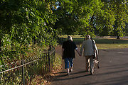 A devoted elderly couple show their love by holding hands as they walk in late afternoon sunshine through Ruskin Park, on 8th September 2016, south London borough of Southwark, England UK. Making their way slowly, the old people continue through the park with shadows on a brick wall behind them.