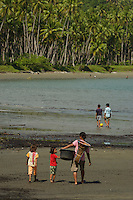 Woman and girls walk on beach at Labilabi, Halmahera, Indonesia.